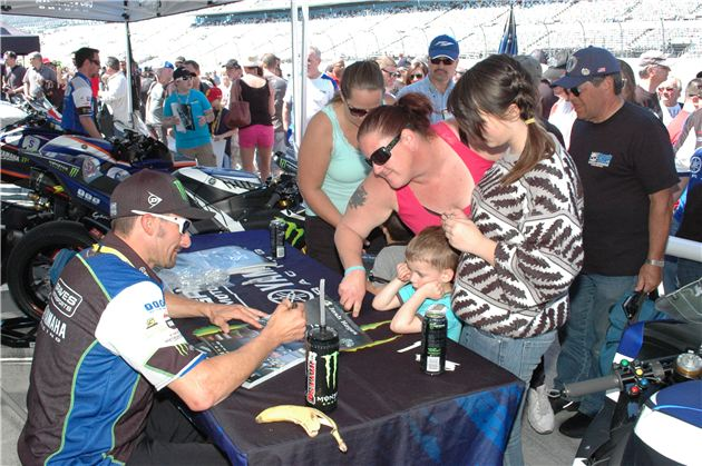 Three-time Superbike Champion Josh Hayes signs posters for fans.